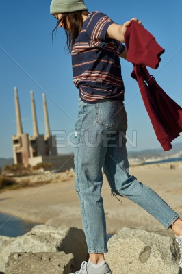 A happy young lady walking on rocks