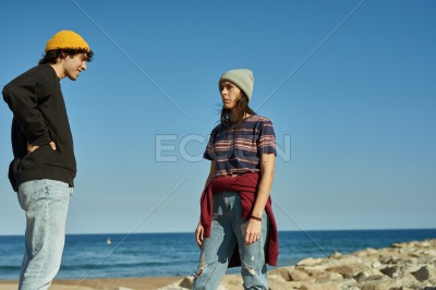 Two airy young people casually standing on rocks