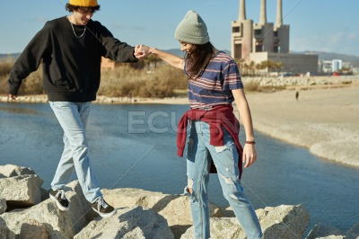 Two blissful people helping each other climb rocks