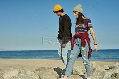 Two blissful young people walking along the beach