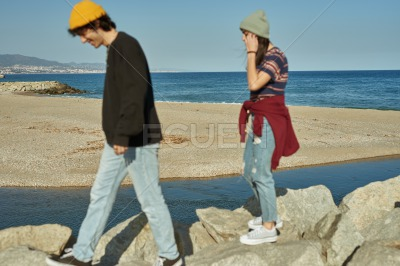 Two engaged young people walking on rocks