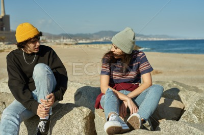Two riveted young people sitting on rocks