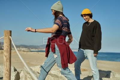 Two spirited young people climbing on rocks