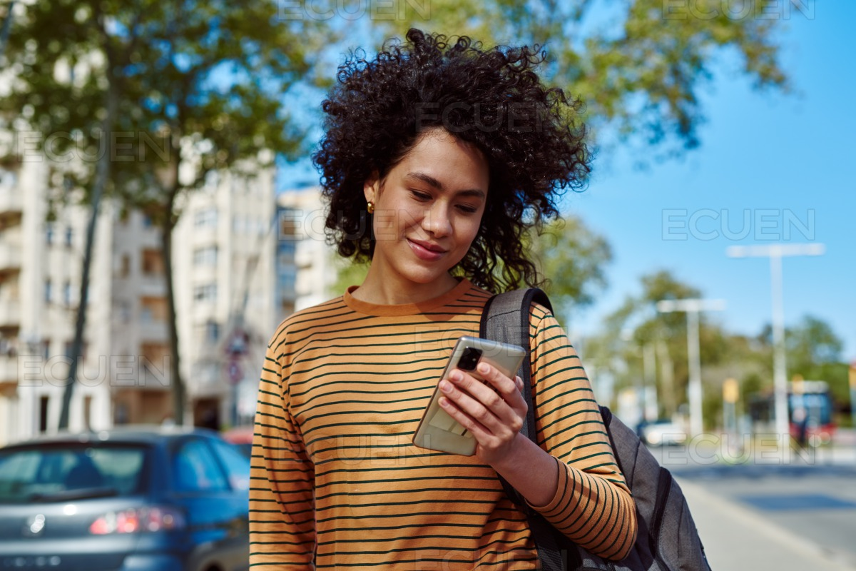 Cute young woman reading a message while walking stock photo