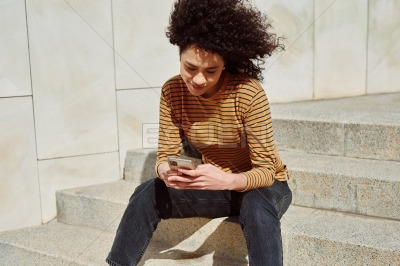 Cute girl reading a text message outdoors
