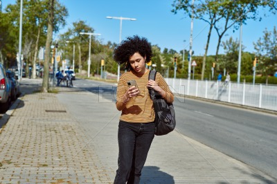 Cute young woman using a cellphone on her way