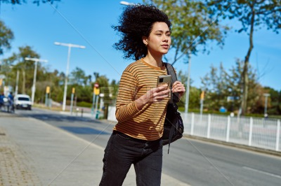 Cute young woman using a cellphone while running
