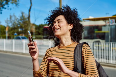 Laughing young woman holding a cellphone outdoors