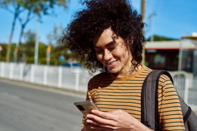 Smiling young woman reading a text by the roadside