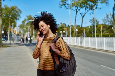 Smiling young woman taking a call by the roadside