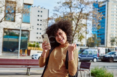 Young woman celebrating while holding a cellphone