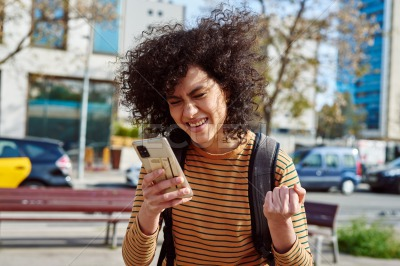 Young woman celebrating while using a cellphone